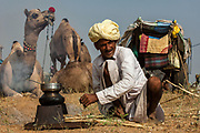 Pushkar camel and livestock fair which takes place in the Hindu month of Kartik (October / November) ten days after Diwali (Festival of Lights). Pushkar has always been the the region's main market for herdsman and farmers buying and selling camels, horses, indigenous breeds of cattle and even elephants. Over the years this annual trading event has increased in volume to become one of the largest in Asia. Temporary tents and campsites suddenly appear to accomodate the thousands of pilgrims, villagers and tourists. Entertainers and contests abound and a festive funfair atmosphere prevails over Pushkar during the Mela's 2 week duration. Thousands of men come first with their camels, horses and cattle and camp on the dunes to transact business. 3 days before the full moon the women arrive beautifully attired. The town of Pushkar is one of the holiest centers of Hinduism and houses one of the few Brahma Temples in India. It is one of the 5 essential pilgrimage centers which a Hindu must visit in his lifetime along with Badrinath, Puri, Rameshwaram and Dwarka. The 12 day fair culminates in a religious Hindu pilgrimage and reaches a crescendo on the night of the full moon (Purnima) when pilgrims take a dip in the holy lake.  <br /> Pushkar, Rajasthan. INDIA