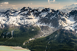 Glaciers flow  into the Wachusett Inlet of the East Arm of Glacier Bay National Park and Preserve.  Peak at upper left is Mount Merriam. In the very distant upper right Mount Bertha, located in the Fairweather Range, can be seen.<br /> <br /> Glacier Bay National Park is located in southeast Alaska. Known for its spectacular tidewater glaciers, icefields, and tall costal mountains, the park is also an important marine wilderness area. The park a popular destination for cruise ships, is also known for its sea kayaking and wildlife viewing opportunities. <br /> <br /> Glacier Bay National Park is home to humpback whales which feed in the park's protected waters during the summer, both black and grizzly bears, moose, wolves, sea otters, harbor seals, steller's sea lions and numerous species of sea birds. <br /> <br /> The dynamically changing park, known for its large, contiguous, intact ecosystems, is a United Nations biosphere reserve and a UNESCO World Heritage site.