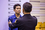 "A Thai immigration police officer helps an undocumented Cambodian worker pose for a ""mug shot"" for a temporary ID card. at the temporary ""one stop service center"" in the Bangkok Youth Center in central Bangkok. Thai immigration officials have opened several temporary ""one stop service centers"" in Bangkok to register undocumented immigrants and issue them temporary ID cards and work permits. The temporary centers will be open until August 14."