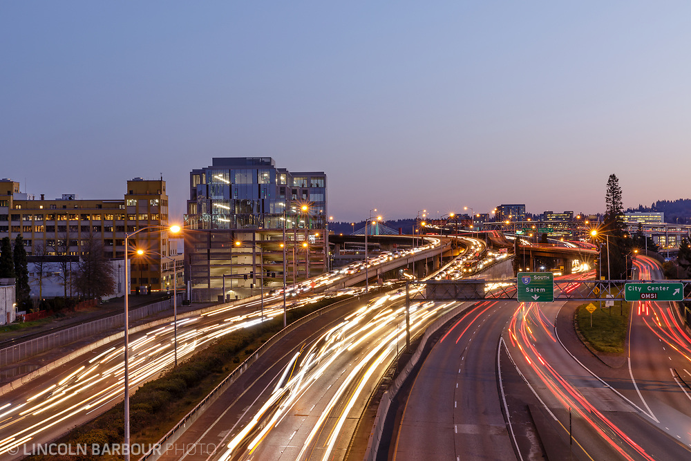 The 7 Stark Building stands over the 5 freeway at dusk as car lights streak by from the evening commute in Portland, Oregon.