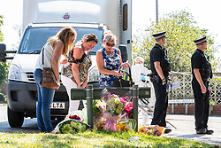 © Licensed to London News Pictures. 28/05/2018. Stockport, UK. Three women bring flowers to the scene outside The Salisbury Club on Truro Avenue in the Brinnington area of Stockport, Greater Manchester, where a car collided with pedestrians late last night, killing one man and injuring others.  A murder investigation has been launched. Police later recovered a black Audi A4 which fled the scene. Photo credit: Joel Goodman/LNP