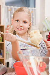 Girl mixing butter in bowl, smiling, portrait
