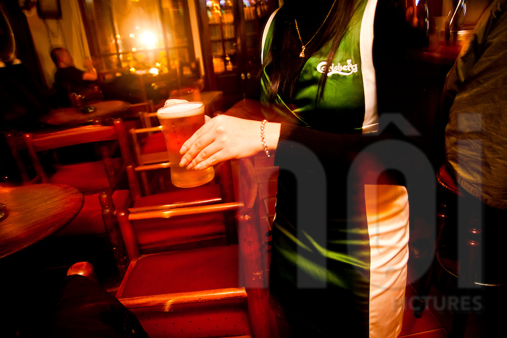 A Carlsberg beer promotion girl carries a beer to a customer in a bar of Hanoi, Vietnam