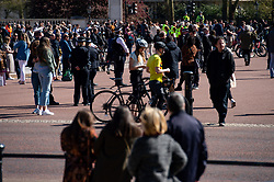 People observe a minute's silence outside Buckingham Palace, London, as the funeral of the Duke of Edinburgh takes place in St George's Chapel, at Windsor Castle, Berkshire. Picture date: Saturday April 17, 2021.