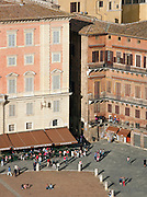 The Piazza del Campo, seen from above, has many bars and restaurants, and is busy with tourists and locals in Siena, Tuscany, Italy