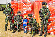 """11 JANUARY 2014 - BANGKOK, THAILAND: A Thai boy poses for photos with Thai special forces soldiers during an Army open house on Children's Day. The Royal Thai Army hosted a """"Children's Day"""" event at the 2nd Cavalry King's Guard Division base in Bangkok. Children had an opportunity to look at military weapons, climb around on tanks, artillery pieces and helicopters and look at battlefield medical facilities. The Children's Day fair comes amidst political strife and concerns of a possible coup in Thailand. Earlier in the week, the Thai army announced that movements of armored vehicles through Bangkok were not in preparation of a coup, but were moving equipment into position for Children's Day.      PHOTO BY JACK KURTZ"""