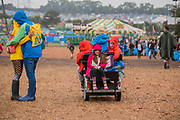 A couple hu and children enjoy the ride on their Dad's buggy. A bit of light rain brings out the waterproofs but wellies are a split decision - The 2017 Glastonbury Festival, Worthy Farm. Glastonbury, 23 June 2017