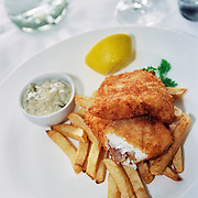 A plate of traditional fish and chips with tartar sauce.