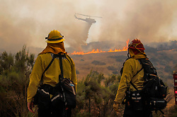 May 20, 2017 - Jamul, California, U.S. - Firefighter JUSTIN HEISER, left, and Fire Captain JOHN BURNINGHAM, both with Viejas Fire Department, watch as a helicopter drops water on flames as a brushfire burns next to Otay Lakes Road near Highway 94. (Credit Image: © Hayne Palmour Iv/San Diego Union-Tribune via ZUMA Wire)