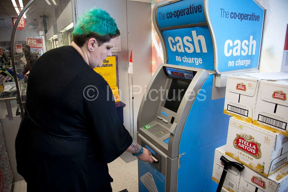 Mother Louise Irwin-Ryan gets some cash from the ATM cash point machine in her local supermarket in her neighbourhood of Barnsbury, near to Kings Cross, North London. Louise is on various benefits to help support her family income, and housing, although recent government changes to benefits may affect her family drastically, possibly meaning they may have to move out of London. Louise Ryan was born on the Wirral peninsula in 1970.  She moved to London with her family in 1980.  Having lived in both Manchester and Ireland, she now lives permanently in North London with her husband and two children. Through the years Louise has battled to recover from a serious motorcycle accident in 1992 and has recently been diagnosed with Bipolar Affective Disorder. (Photo by Mike Kemp/For The Washington Post)