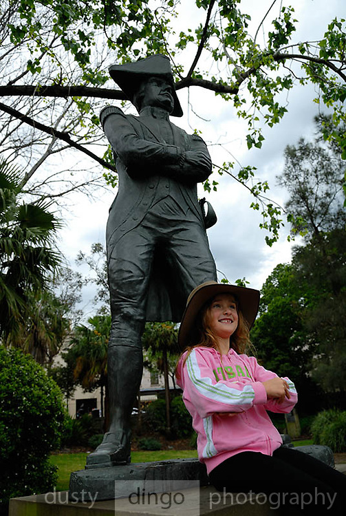 Child (6 years old) sitting at feet of statue of Captain Bligh. Circular Quay, Sydney, Australia