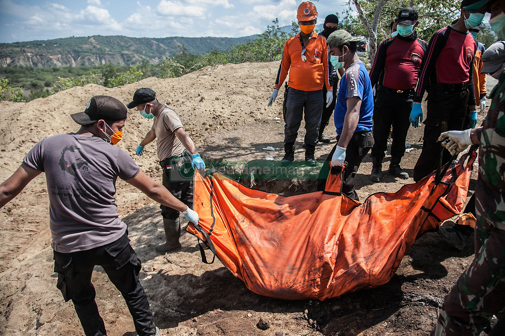 October 3, 2018 - Palu, Central Sulawesi, Indonesia - Indonesian rescuers carry the body bag of a disaster victim during a mass burial at a field, after earthquake and tsunami on September 28. Indonesian government on October 2 said the death toll from a devastating quake-tsunami on the island of Sulawesi had risen to 1,234 people, up from the previous count of 844 have been confirmed dead slammed into Indonesia's coastline on the island of Sulawesi, causing thousands of homes to collapse, along with hospitals, hotels and shopping centers.  (Credit Image: © Ivan Damanik/ZUMA Wire)
