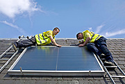 Workmen installing a solar thermal panel on the roof of Pinmore ceramics gallery, they have received advice from the Energy agency, Ayrshire.<br /> Solar water heating systems use heat from the sun to work alongside your conventional water heater