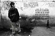 """A Huelepega urinates on a wall in Managua, Nicaragua on February 12, 2007. The stencil on the wall reads, """"Look, sons of a thousand whores, do not urinate shit or leave trash here. Got it, son's of a bitches."""".Nicaragua has known chronic war and poverty, forces that over time can break the fabric that holds families together. In a Society where poor single mothers are common and must provide for large families in Latin America's most devastated economy, it is inevitable that children are forced to choose between abuse and hunger in the home, or the street. A growing number have been choosing the street. Most get addicted to glue. Called Huelepegas, or glue sniffers they are ostracized far beyond the lowest rung of society. Although NGOs have cobbled together a few basic services to support the children, it is up to President Ortega's new socialist government to address this growing problem after years of neglect."""