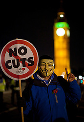 © Licensed to London News Pictures .A demonstrator joins the People's Assembly national day of action and march along Westminster Bridge to protest against rising energy bills and cuts in the NHS. (05/11/2013) . Photo credit : Isabel Infantes /LNP