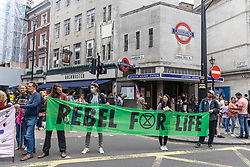 """Licensed to London News Pictures. 23/08/202. London, UK. Climate change protesters Extinction Rebellion (XR) block St Martin's Lane in Covent Garden, London at the start of a 14 day protest with disruptive action and possible occupations of buildings and services. The protest, """"The Impossible Rebellion"""", want the government to implement their demand to stop all new fossil fuel investment immediately. Photo credit: Alex Lentati/LNP"""