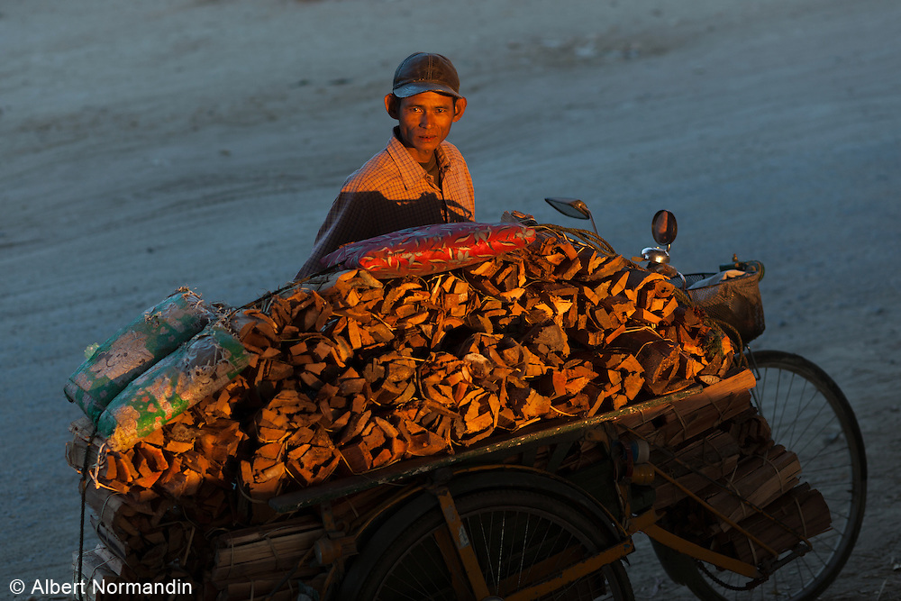 Man with his Trishaw full of wood to deliver at sunset light