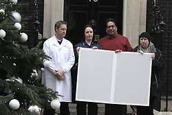 © London News Pictures 20/12/2011. London, UK. Health workers who are members of the Unison, Unite and GMB unions this morning presented a giant 'Scrooge' Christmas card to 10 Downing Street, which contains a petition with 10,000 signatures against the Health and Social Care Bill. Photo credit: Brian Duckett/LNP