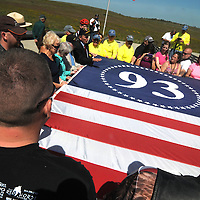 Visitors to the Memorial Plaza pauses to unfold a flag at the entrance of the Flight 93 National Memorial near Shanksville, Pa.,  on the 14th observance of the Flight 93 crash and Sept. 11 terrorist attacks. Photo by Archie Carpenter/UPI .