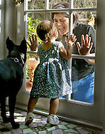 Cara Sodos Teitelbaum and daughter Emily Rose Teitelbaum share a fun moment at the front porch door of their home as their dog Reggie looks on.