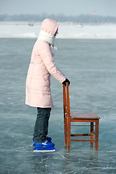 Young girl using wooden chair for balance whilst learning to ice skate on the frozen Songhua River during winter in Harbin China