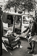 A handicapped woman sits down in a chair to be carried at the Varanasi (Benares) train station in India.