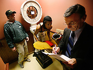 Tony Marco, right, the clerk of scales, weighs in jockey Sylvia Harris, center, as Kenny Rice stands by in the jockey room at Hawthorne Race Course in Stickney, Ill., Sunday, Jan. 13, 2008. Harris raced in two races on Sunday. (AP)