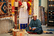 Morocco, Ait Benhaddou. Portrait of a woman working as a weaver.