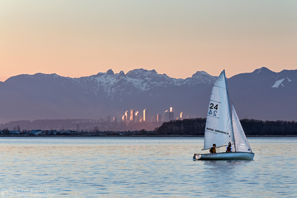 "A small sailboat moves past the beach at Crescent Beach in Surrey, British Columbia, Canada.  The towers in the background are in Burnaby, BC (Metrotown).  The two rounded mountain peaks behind Burnaby are known as ""The Lions""."