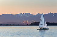 """A small sailboat moves past the beach at Crescent Beach in Surrey, British Columbia, Canada.  The towers in the background are in Burnaby, BC (Metrotown).  The two rounded mountain peaks behind Burnaby are known as """"The Lions""""."""