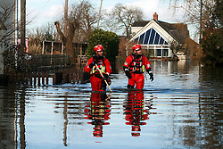 © London News Pictures. 24/02/2014. Moorland, UK. Members of a fire rescue team wade through waist deep flood water in Moorland on the Somerset Levels, which continues to suffer from sever flooding. Photo credit: Jason Bryant/LNP