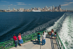 North America, United States, Washington, Seattle, passengers on front deck of ferry, with downtown Seattle in distance