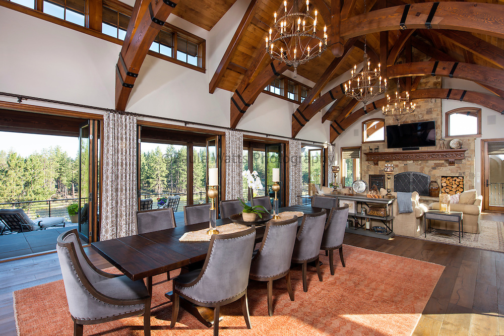 Rustic dining and living room with cathedral ceiling and chandeliers