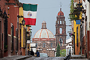A Mexican flag flies over Recreo Street with the dome of San Francisco Church in San Miguel de Allende, Mexico.