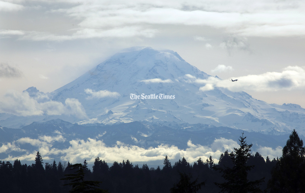 Under partly sunny skies, after taking off from Seattle-Tacoma International Airport a plane passes by Mt. Rainier. (Ellen M. Banner / The Seattle Times)