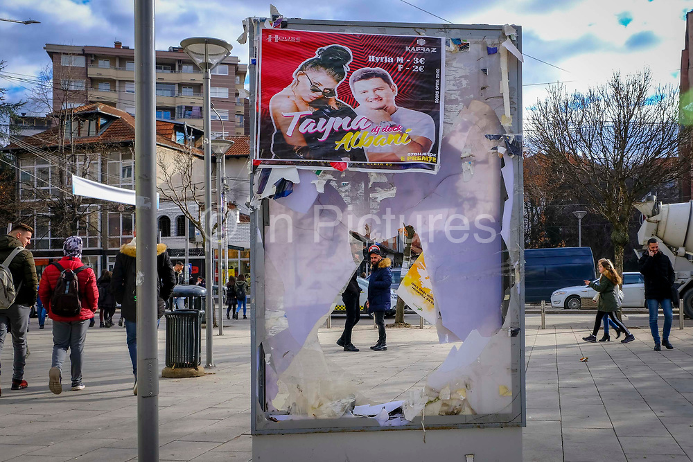 A man looks through a disused advertising board in the shopping area in the south side of Mitrovica, a town in Northern Kosovo that straddles the river Ibar that separates the Serbian and Albanian districts of Mitrovica, Kosovo on the 12th of December 2018.  Mitrovica or Kosovska Mitrovica is a city and municipality located in Northern Kosovo.