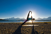 A young woman practices yoga on the shore of Jackson Lake in Grand Teton National Park, Jackson Hole, Wyoming.