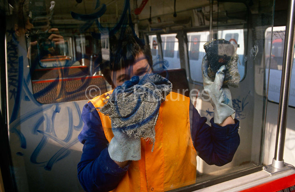 A London Underground employee wipes hard to remove the tagging left behind by permanent marker pens on London Transport property. A youth has committed the crime of defacement and criminal damage to London Underground property, a persistent problem that costs the transport company network up to £3 million a year to remove. Partitions and glass are being scribbled on with their unique identity signatures used by kids of this age to leave as a mark of their presence, like animals instinctively leave a scent on a street corner. If caught, juvenile delinquents like these may escape with only a caution because of their age but older ones are prosecuted, though some times after leaving many thousands of tags across their neighbourhood.