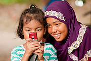 """Sept. 27, 2009 -- RANGAE, THAILAND: Muslim girls play with a cell phone camera near their family home in Rangae, Narathiwat, Thailand. Thailand's three southern most provinces; Yala, Pattani and Narathiwat are often called """"restive"""" and a decades long Muslim insurgency has gained traction recently. Nearly 4,000 people have been killed since 2004. The three southern provinces are under emergency control and there are more than 60,000 Thai military, police and paramilitary militia forces trying to keep the peace battling insurgents who favor car bombs and assassination.   Photo by Jack Kurtz"""