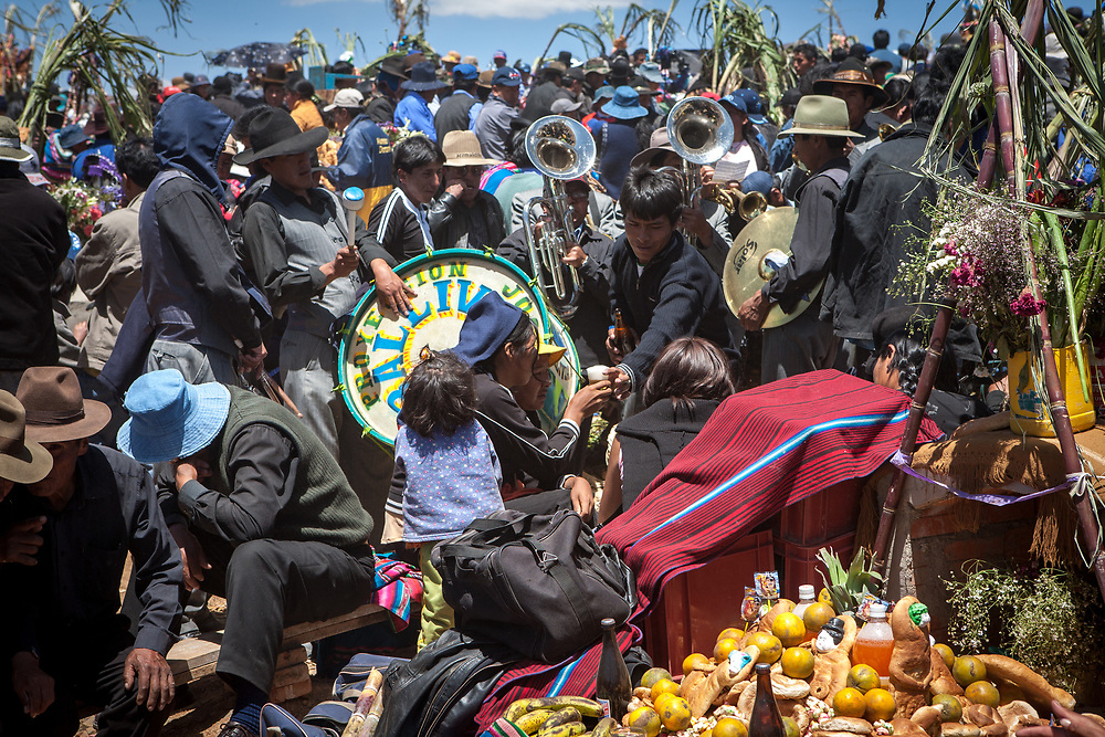Crowds throng a graveyard on the day of the dead in the Bolivian altiplano. A traditional brass band with accompanying percussion plays tunes at gravesides, people eat and drink.