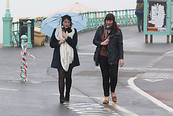 © Licensed to London News Pictures. 01/05/2016. Brighton, UK. Two woman shelter under a umbrella as the weather has turned cold and wet on the last day of the May Bank Holiday weekend. Photo credit: Hugo Michiels/LNP