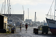 © Licensed to London News Pictures. 01/12/2013. Southwold, UK. Two joggers make their way through the harbour. The first of December was greeted by a brisk sunny morning at the harbour on the River Blyth in Southwold, Suffolk today, 1st December 2013. Photo credit : Stephen Simpson/LNP