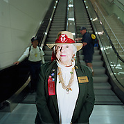 Sheryl is an Airport Ambassador Volunteer at Dallas Fort Worth, Texas and stands for a portrait at the foot of some escalators in the main terminal. She sports a straw hat saying 'Ask Me' in red and a name badge with her job title although she comes to the airport to assist strangers at her city's airport, hoping her good nature and charitable efforts will help uncertain travellers find their way. Also on her jacket is a the phrase 'Proud to be Drug Free .. Airport Narcotics Task Force.' 'Fort Worth is the sixth busiest airport in the world transporting 59,064,360 passengers in 2005. Picture from the 'Plane Pictures' project, a celebration of aviation aesthetics and flying culture, 100 years after the Wright brothers first 12 seconds/120 feet powered flight at Kitty Hawk,1903..