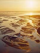 Alan White flying his Cessna 185 over mudflats where the Matanuska and Knik rivers drain into Knik Arm of Cook Inlet, Alaska.