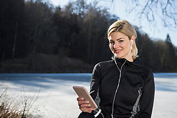 Young female jogger having a break while listening music on smart phone