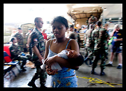 30th August, 2005. Triage at the Superdome in New Orleans. A young mother carries her baby into safety at the Superdome having been rescued from the flooded lower 9th ward by the Louisiana National Guard.