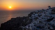 Classic beautiful sunset view of Oia with windmills in the distance on Santorini, Greece.