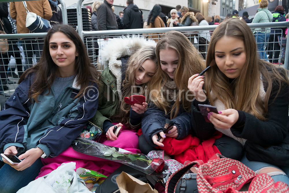 Girls waiting to see their favourite movie stars outside the BAFTA Awards ceremony in London, England, United Kingdom. Elena, Izzy, Bella and Azzurra doing their make up while they wait under blankets in the cold. Izzy has a red rose she hopes to give to Leonardo DiCaprio. (photo by Mike Kemp/In Pictures via Getty Images)