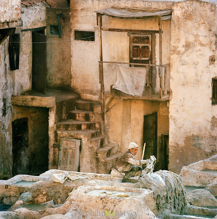 A man working and dyeing leather in the Tannery in Fes, Morocco