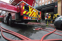 Soho, London, May 8th 2015. Firefighters deal with a fire that broke out at lunchtime in the kitchens of Carom and Floridita, a pair of Wardour Street restaurants in the heart of Soho. The cause is still being investigated. PICTURED: Firefighters take a breather outside the scene of the fire.
